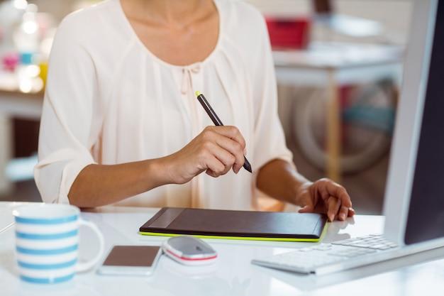 Kobieta Za Pomocą Tabletu Graficznego Premium Zdjęcia