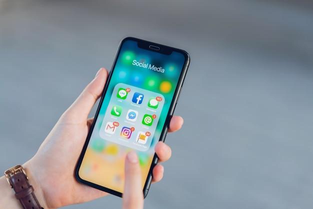 Kobieta za pomocą telefonu aplikacji wyświetlania pokazu ekran mediów społecznościowych. Premium Zdjęcia