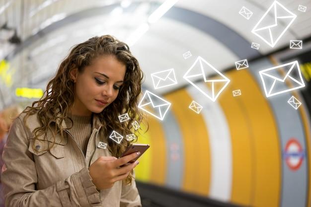 Kobieta za pomocą telefonu komórkowego na stacji metra metra w londynie Premium Zdjęcia