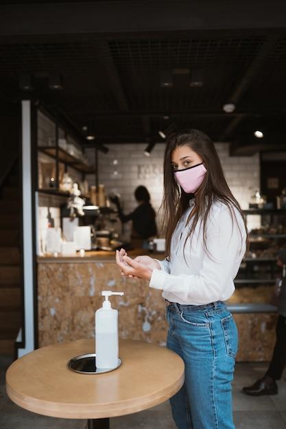 Kobieta Za Pomocą żelu Dezynfekującego Czyści Ręce Wirusa Koronawirusa W Kawiarni. Darmowe Zdjęcia