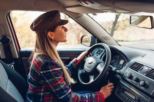 Kobieta zaczyna swój samochód. młody kierowca wkłada kluczyki do stacyjki i jest gotowy do pracy. właściciel włącza auto Premium Zdjęcia