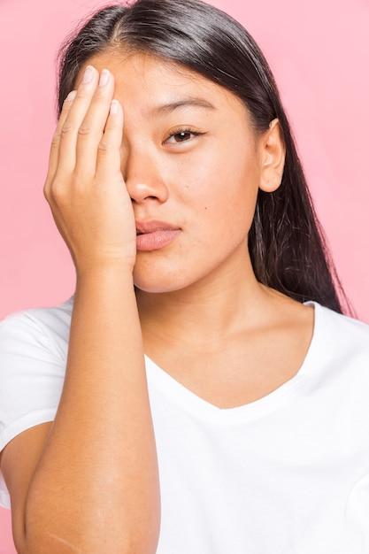 Kobieta zasłaniając twarz jedną ręką Darmowe Zdjęcia