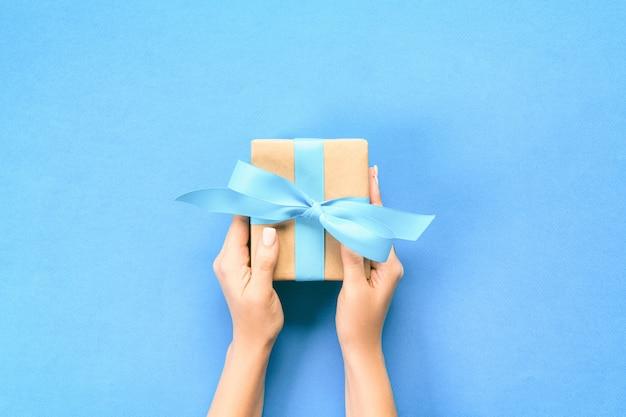 Kobieta Zbroi, Trzymając Pudełko Z Niebieską Wstążką Na Niebiesko Premium Zdjęcia