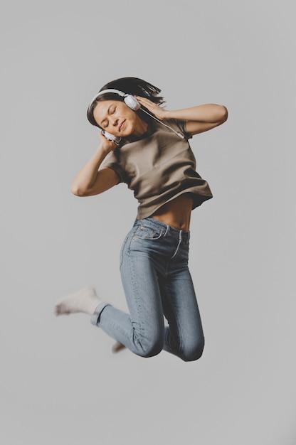 Kobieta Ze Słuchawkami Skacząca W Powietrzu Darmowe Zdjęcia
