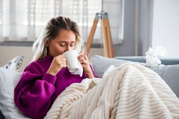 Kobieta złapała przeziębienie i grypę kichającą w tkankę. Premium Zdjęcia