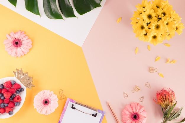 Kobiety Biznesowy Miejsce Pracy Z Laptopem, Kwiatami I Zielonym Palmowym Liściem Na Jaskrawym Tle żółtym I Różowym. Widok Z Góry Przestrzeni Roboczej Kobiety W Okresie Letnim. Leżał Płasko Premium Zdjęcia