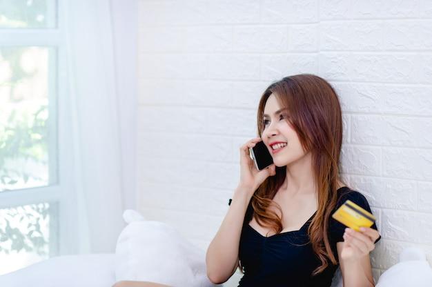 Kobiety biznesu rozmawiają przez telefon i patrzą na kartę kredytową Premium Zdjęcia