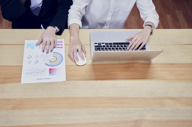 Kobiety biznesu używają laptopów i dokumentów finansowych do pracy w biurze. Premium Zdjęcia