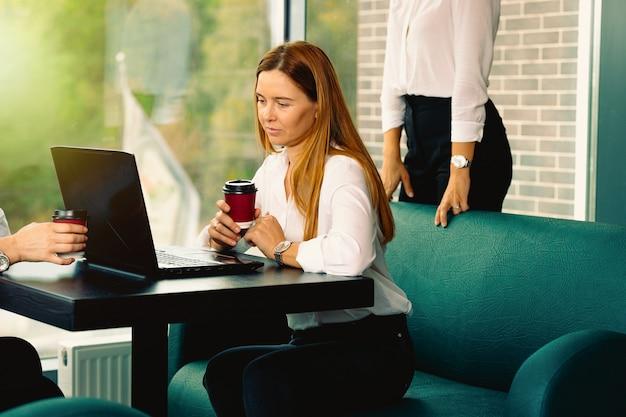 Kobiety Biznesu W Eleganckich, Wizytowych Strojach Dyskutują O Sprawach, Używając Laptopa, Pijąc Kawę I Uśmiechając Się Podczas Współpracy W Kawiarni. Spotkanie Biznesowe W Nowoczesnym Wnętrzu W Stylu Loftu Z Cegły Premium Zdjęcia