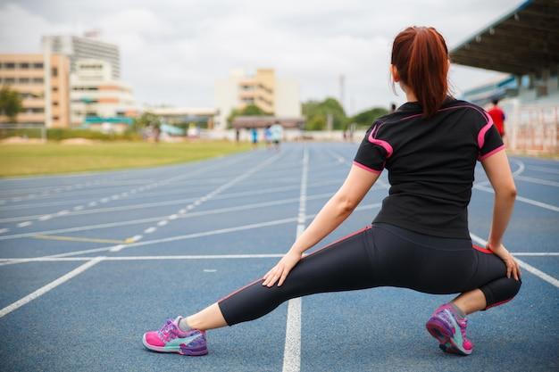 Kobiety ćwiczące. młoda kobieta fitness ćwiczenia w słoneczne jasne światło rano na niebieskim gumowanym bieżni. Premium Zdjęcia