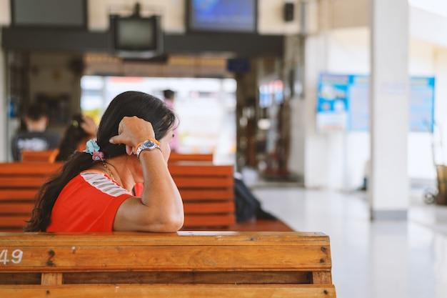 Kobiety dosypianie w przystankach autobusowych z miękką ostrością i nadmiernym światłem w tle Premium Zdjęcia