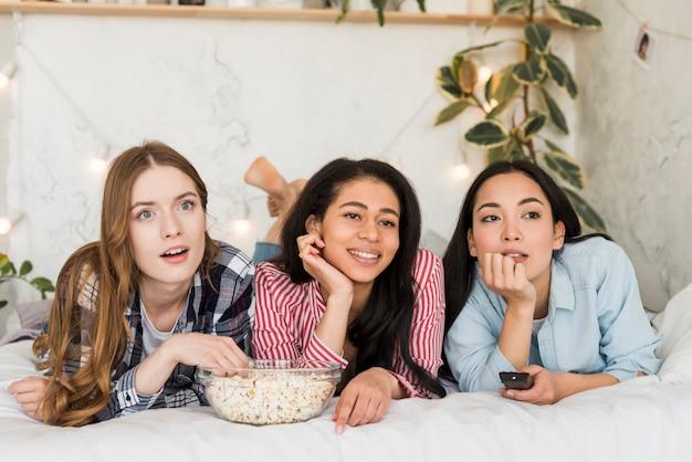 Kobiety leżące na łóżku i oglądające telewizję Darmowe Zdjęcia
