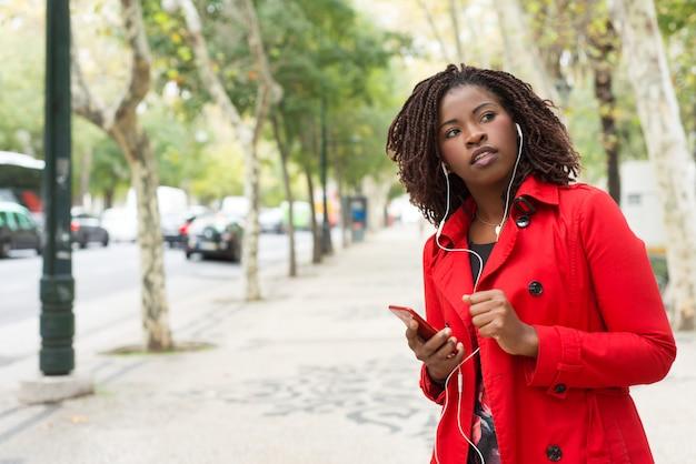 Kobiety Mienia Smartphone I Przyglądająca Strona Na Ulicie Darmowe Zdjęcia