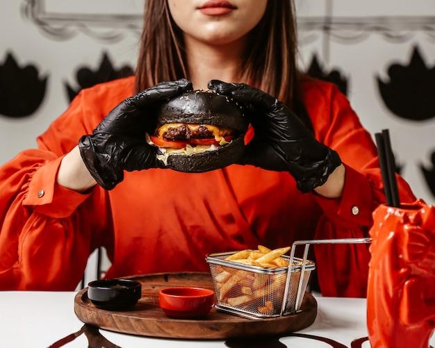 Kobiety Mienie W Ona Ręki Cheeseburger Z Czarną Babeczką Darmowe Zdjęcia