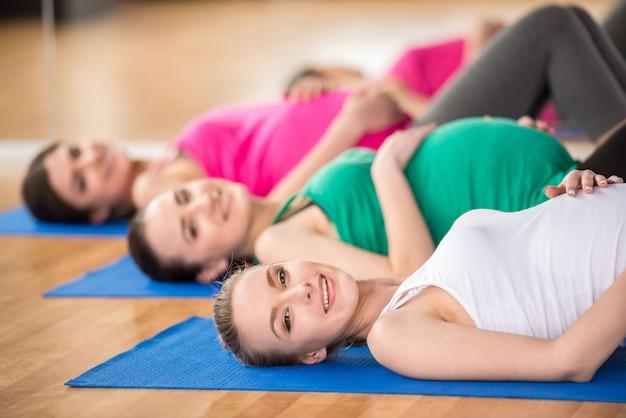 Kobiety na zajęciach jogi leżą na matach w studiu fitness. Premium Zdjęcia