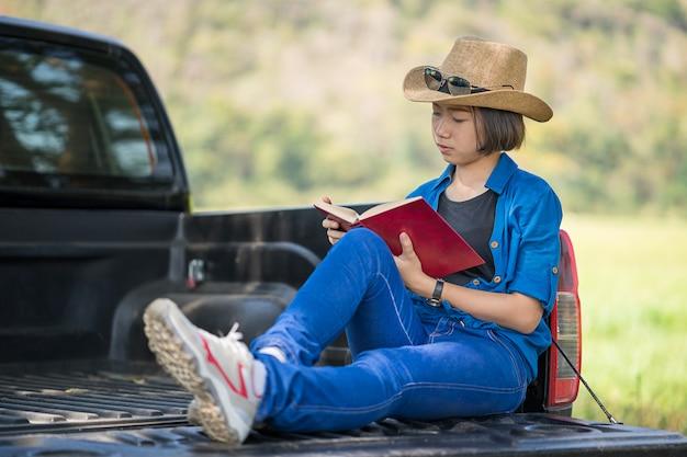 Kobiety noszą kapelusz i czytając książkę na furgonetkę Premium Zdjęcia