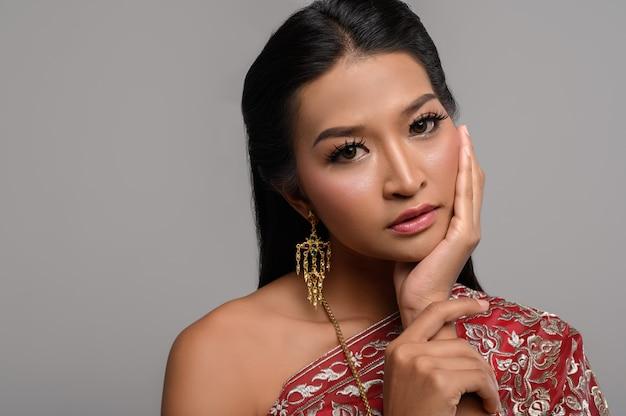 Kobiety noszące tajskie ubrania i dłonie dotykające twarzy Darmowe Zdjęcia