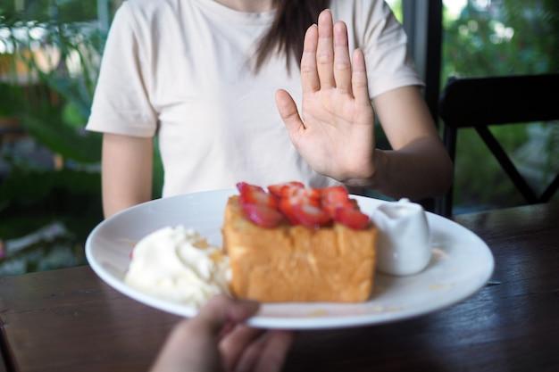 Kobiety odmawiają jedzenia słodyczy dla utraty wagi i dobrego zdrowia. Premium Zdjęcia