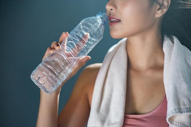 Kobiety po treningu piją wodę z butelek i chusteczek na siłowni. Darmowe Zdjęcia
