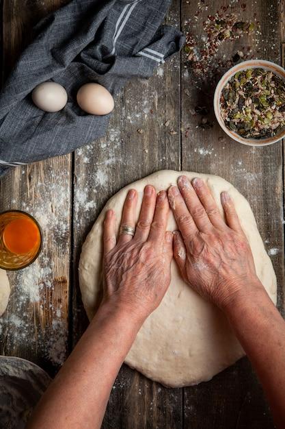 Kobiety Podesłania Ciasto Z Rękami Na Drewnianym Stołowym Odgórnym Widoku. Darmowe Zdjęcia