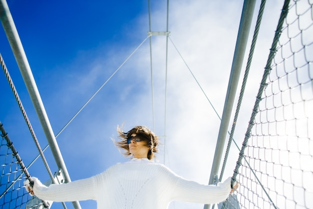 Kobiety pozycja na bridżowej wysokości w niebie Darmowe Zdjęcia