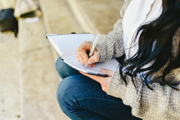 Kobiety Ręka Bierze Notatki W Jej Notatniku Z Piórem, Siedzi. Premium Zdjęcia