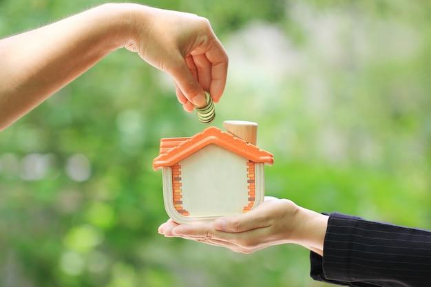 Kobiety ręka stawia monetę w drewnianego dom na naturalnym zielonym tle Premium Zdjęcia