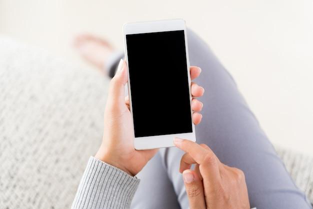 Kobiety Ręka Trzyma Białego Telefon Komórkowego I Obsiadanie Na Kanapie W Domu Premium Zdjęcia