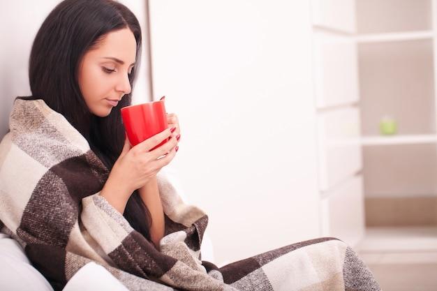 Kobiety ręka trzyma czerwoną filiżankę kawy. z pięknym zimowym manicure. pij, modę, rano Premium Zdjęcia