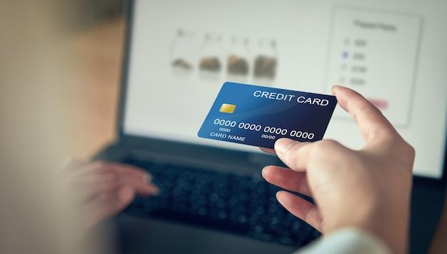 Kobiety ręka trzyma kartę kredytową i naciśnij laptop wpisz kod płatności za produkt. Premium Zdjęcia