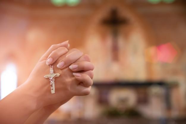 Kobiety ręka trzyma różaniec przeciw krzyżowi i modli się do boga przy kościół Premium Zdjęcia