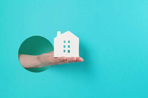 Kobiety Ręka W Papierowej Dziurze Trzyma Małego Zabawka Dom Premium Zdjęcia
