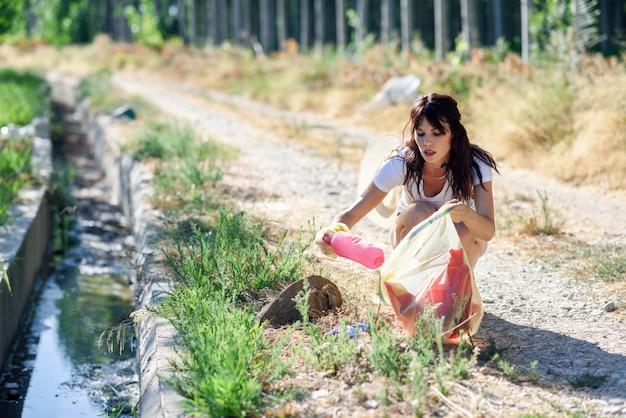 Kobiety Ręka Zbiera śmieci Trawa W Wsi Premium Zdjęcia
