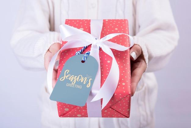 Kobiety Ręki Mienia Prezenta Czerwony Pudełko I Papierowa Etykietka Odizolowywający Na Bielu Premium Zdjęcia