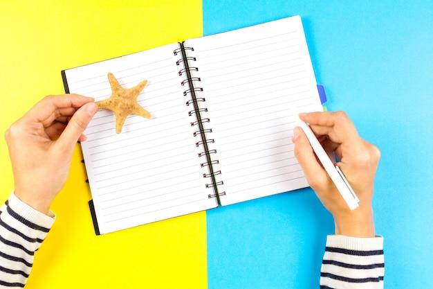 Kobiety Ręki Writing W Otwartym Podróż Notatniku Nad Błękitnym I żółtym Tłem Premium Zdjęcia