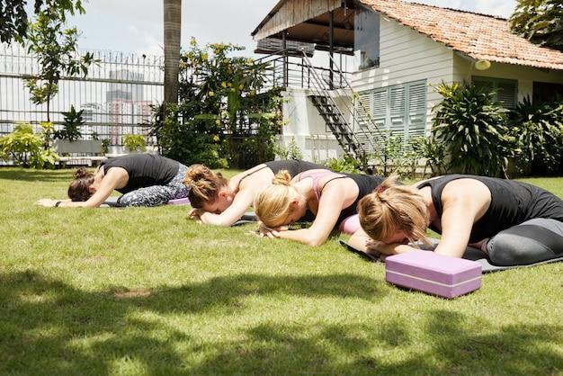 Kobiety rozciąga się na zielonej trawie outdoors z ich głowami odpoczywa na rękach w dziecko pozie Darmowe Zdjęcia