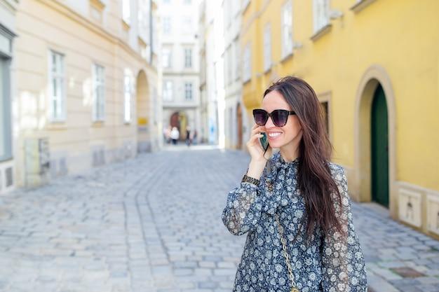Kobiety rozmowa jej smartphone w mieście. młody atrakcyjny turysta outdoors w włoskim mieście Premium Zdjęcia