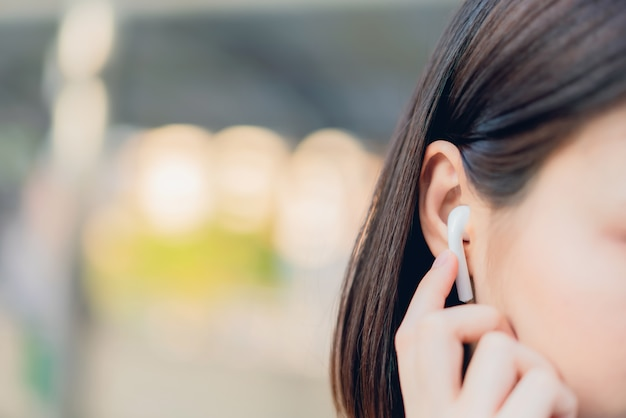 Kobiety słuchają muzyki z białych słuchawek. za pomocą dotyku rąk korzystasz z różnych funkcji, radosnego nastroju. Premium Zdjęcia