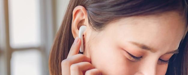 Kobiety słuchają muzyki z białych słuchawek. Premium Zdjęcia
