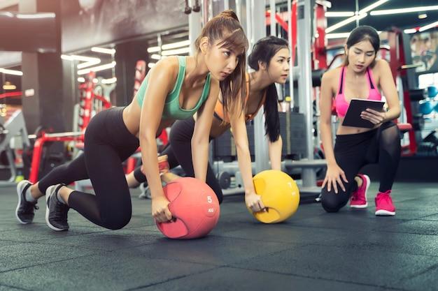 Kobiety Sportowe ćwiczą Razem W Siłowni Z Trenerem Premium Zdjęcia