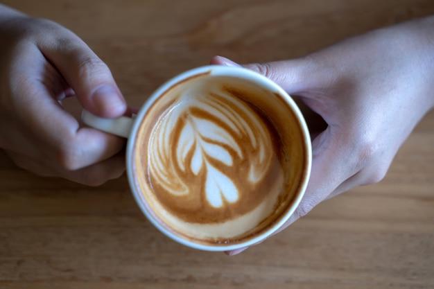 Kobiety Trzyma Filiżankę, Drewniana Stołowa Kawiarnia Podczas Gdy Mieć Kawę Premium Zdjęcia