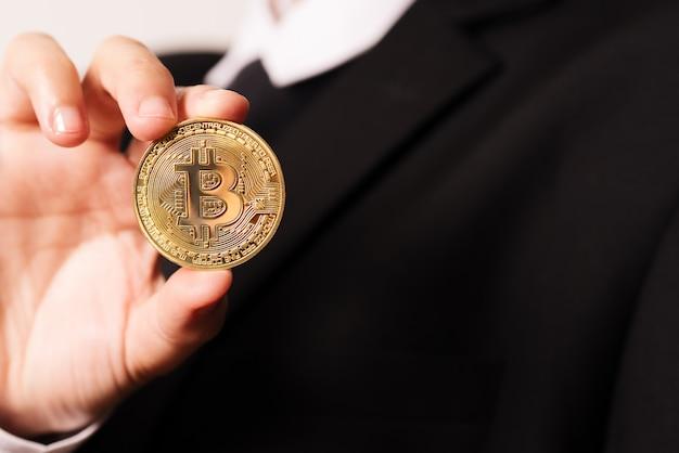 Kobiety trzymają pod ręką monetę kryptowaluty. Premium Zdjęcia