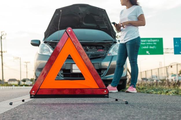 Kobiety używające telefonu komórkowego do robienia zdjęć swojego samochodu, który otwiera kaptur. Premium Zdjęcia