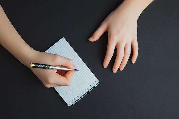 Kobiety writing w notepad przy czerń stołem Premium Zdjęcia