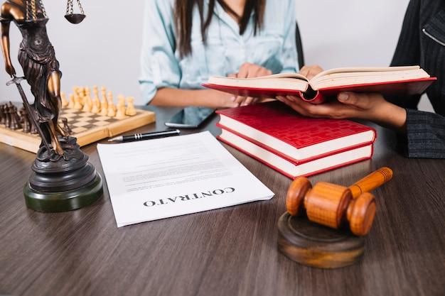 Kobiety z książkami przy stole z smartphone, statua, dokument i szachy Darmowe Zdjęcia