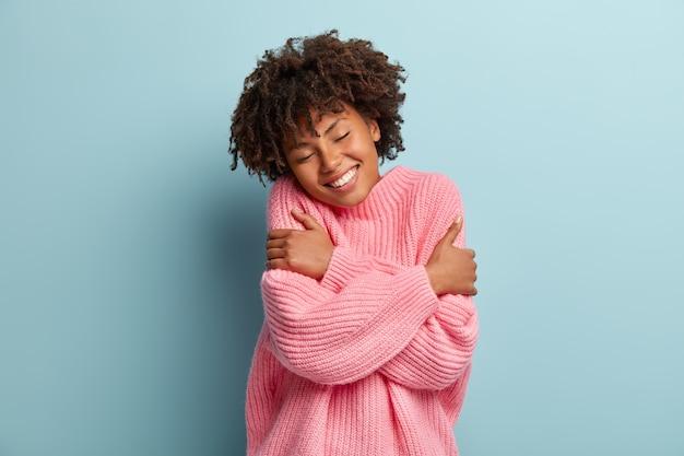 Kochaj Swoją Koncepcję. Zdjęcie Uroczej Uśmiechniętej Kobiety Obejmuje Się, Ma Wysoką Samoocenę, Zamyka Oczy Z Radości Darmowe Zdjęcia