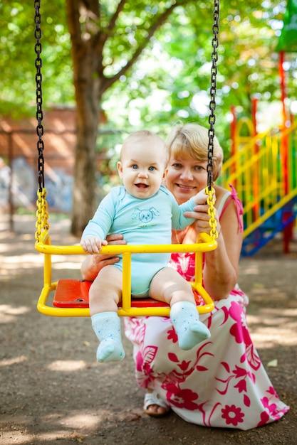 Kochająca Matka Przytula Swojego Małego Syna Na Placu Zabaw. Portret Pięknej Matki Z Dzieckiem Premium Zdjęcia