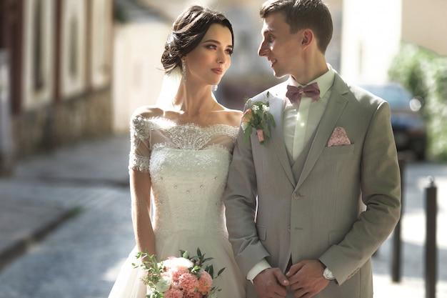 Kochająca para nowożeńców chodzi po mieście i się uśmiecha, Premium Zdjęcia