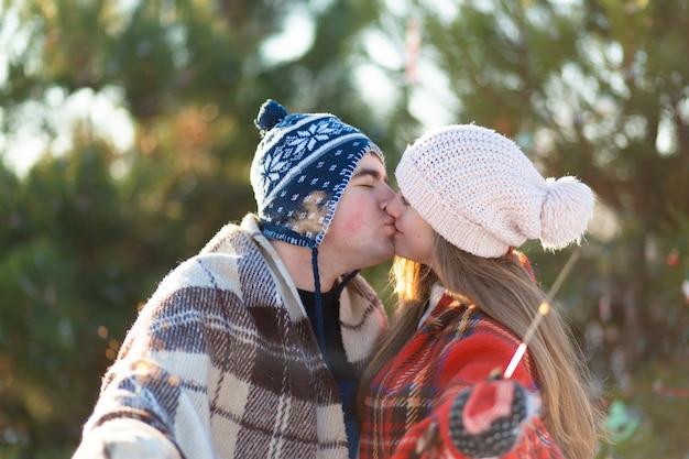 Kochająca para w ciepłych pledach całuje trzymając w rękach sparklers, poznaj ferie zimowe w śnieżnym lesie Premium Zdjęcia