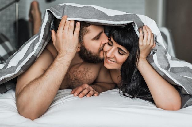 Kochająca Para W łóżku Uprawia Seks. Facet I Dziewczyna Całuje W łóżku. Noc Poślubna. Kochać Się. Kochankowie W łóżku. Relacja Mężczyzny I Kobiety. Seks Między Mężczyzną A Kobietą. Uściski W łóżku. Premium Zdjęcia